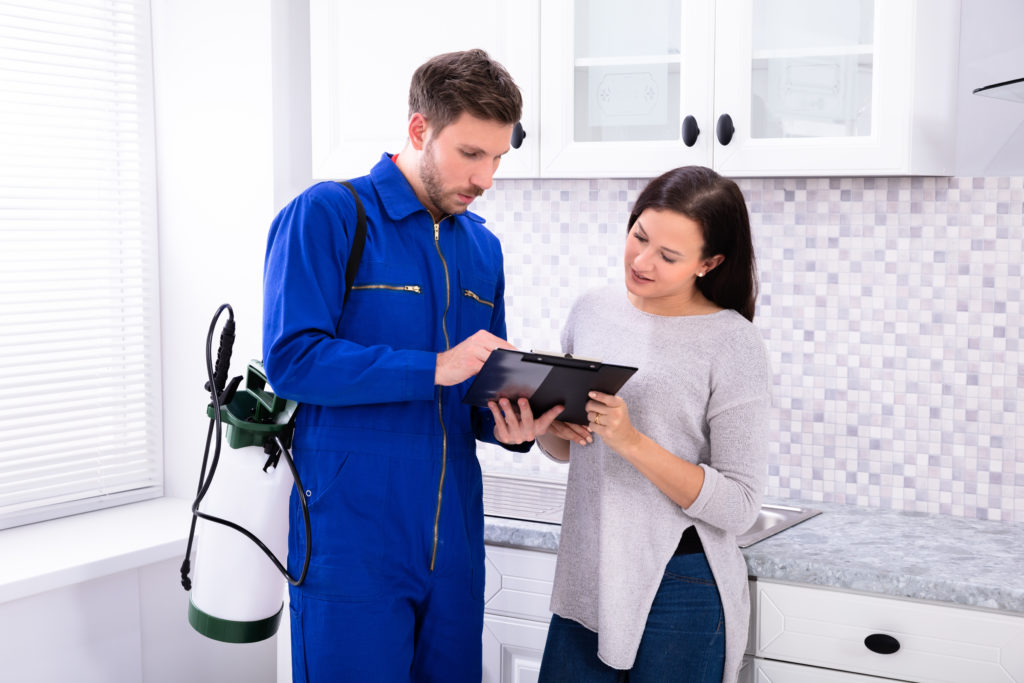 A pest control technician showing a customer an iPad