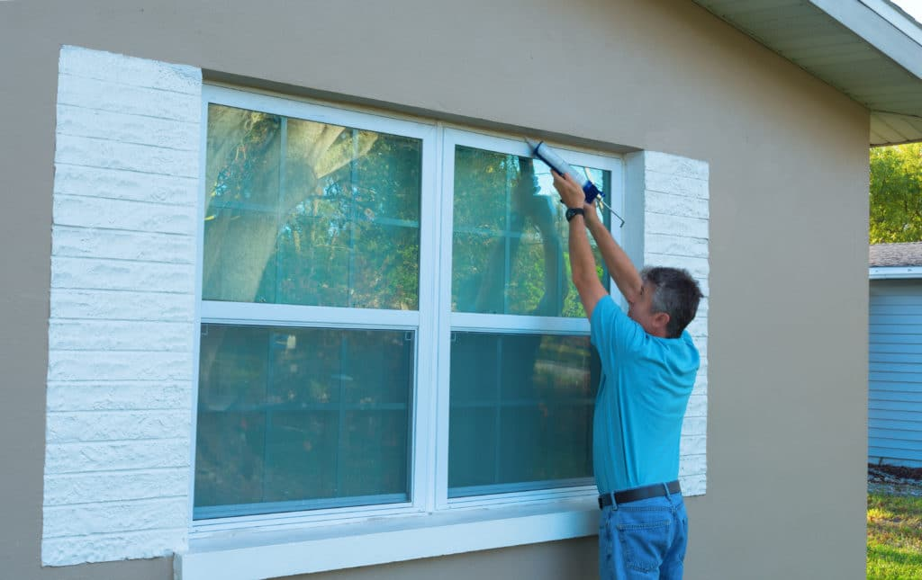 A man caulking the exterior of his home to prevent an earwig infestation
